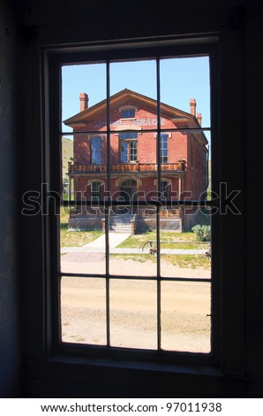 Through a window view of an old house. Ghost town, Bannack State Park, Montana