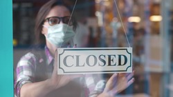 Through glass view of female business owner in safety mask hanging up sign with inscription closed on cafe door. Waitress in protective mask closing restaurant because of pandemic