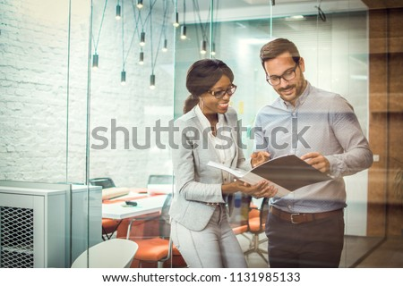 Through glass view of two smiling multi-ethnic business colleagues reviewing paper documents while standing in modern office #1131985133