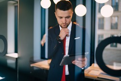 Through glass young pondering businessman wearing formal suit using tablet and touching chin in thoughts while working in contemporary office