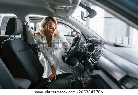 Through open door. Woman in formal clothes is indoors in the autosalon.