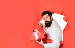 Through paper. Bearded man holds gift box. Valentine's day. Christmas. New year. Birthday. Holidays concept. Man with christmas gift. Attractive man with gift. Businessman holds gift box. Copy space.