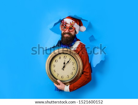 Through paper. Discount. Sale. Christmas sales. Bearded Santa Claus hold clock. Christmas decorations. Delivery gifts. New year gift. New year clock.