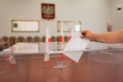 Throwing a card with a voteto the ballot box during  elections. In the backround polish emblem and flag