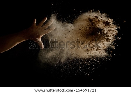 Throwing a Handful of brown earth in the air - isolated on black background