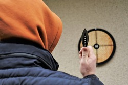 Throwing a knife.Outdoor sports. Black throwing knife in the hand   and a target on the wall.Sport and hobby concept.