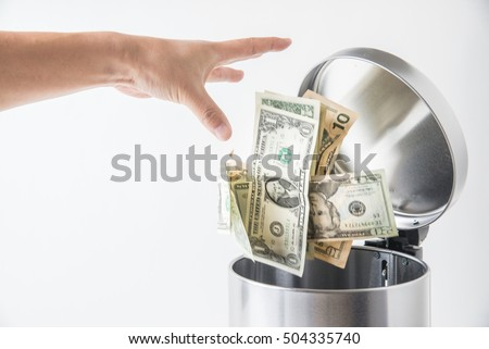 throwing away dollar in trashcan