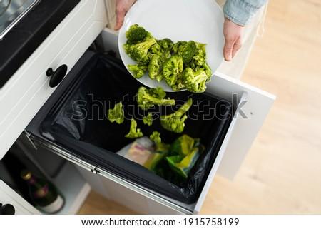 Throwing Away Leftover Food In Trash Or Garbage Dustbin Stockfoto ©