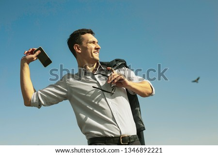 Throwing away phone. Happy stunning man throwing away his phone while quitting from job