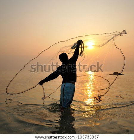 stock photo : throwing fishing net during sunrise, Thailand