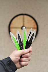Throwing knives. Sport and hobby concept. Throwing knives in a man's hand  and a target on the wall.Outdoor sports. Goal achievement concept.