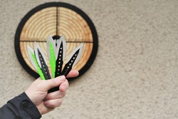 Throwing knives. Sport and hobby concept. Throwing knives in a man's hand close-up and a target on the wall.Outdoor sports. Goal achievement concept.
