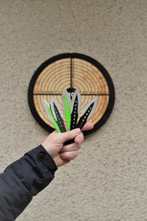 Throwing knives. Sport and hobby concept. Throwing knives in a man's hand close-up and a target on the wall.Outdoor sports. Goal achievement