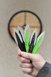 Throwing knives. Sport and hobby . Throwing knives in a man's hand close-up and a target on the wall.Outdoor sports. Goal achievement concept.