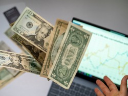 Throwing money on top of a laptop with stock market graph. Stockbrokers bad investment. Dollars flying concept for taxes and interests. Stock investment
