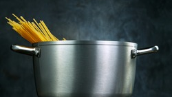Throwing pasta spaghetti into boiled water in steel pot, close-up.
