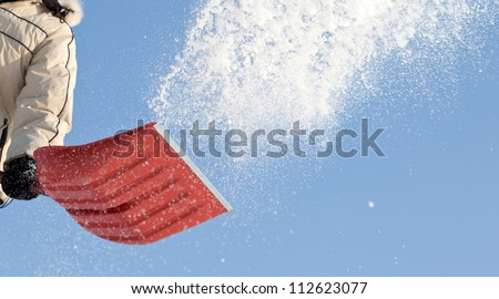 Throwing snow with a snowshovel against blue sky