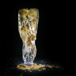 Thrown away plastic bottle with sand from the beach shown like an art sculpture against a black background, waste concept for the  throwaway society that consumes resources and produces micro plastics