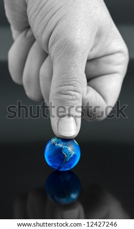 Thumb Pressing Down on Bright Blue Marble Globe