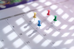 Thumb tacks pin on calendar. Concept for busy schedule.
