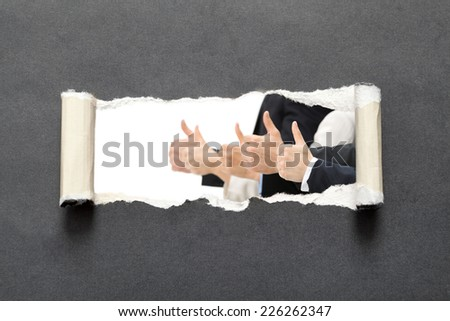 Thumb up businessmen in torn black paper, isolated on black background