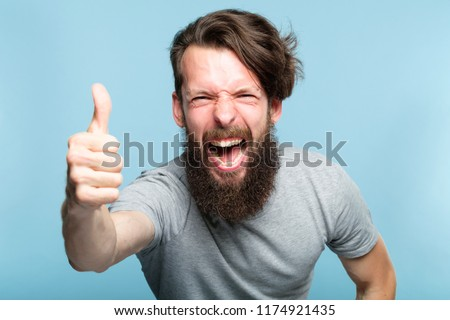 thumb up. good job. like and approval concept. enthusiastic motivated overexcited bearded man showing gesture. cas al hipster guy portrait on blue background.