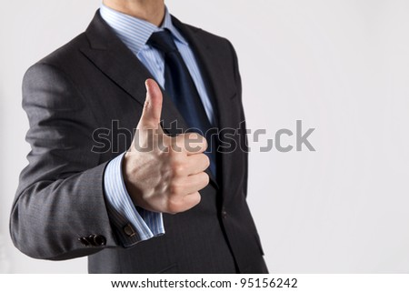 Thumb up, isolated on grey background - stock photo