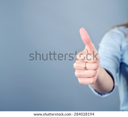 Thumb up. Women\'s hand shows the sign that everything is fine, everything is very good. Woman thumb up on blue background. Space for text. Left, right. Concept about the good things and the good news.