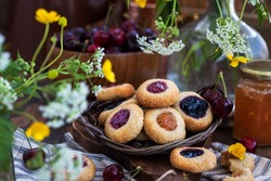 Thumbprint almond cookies with jam on rustic wooden background