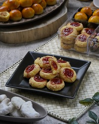 Thumbprint cookies are made from wheat flour, butter, eggs, sugar, then shaped into a round shape and pressed with a thumb, given grated cheese then given strawberry jam and baked until cooked.