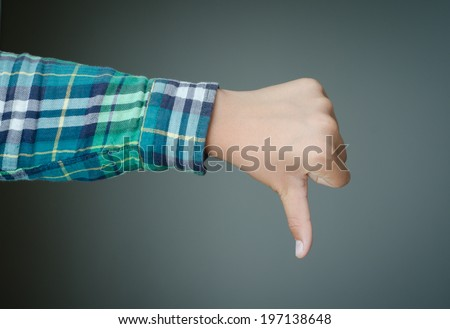 Thumbs down hand, green plaid shirt sleeve, dark green background.