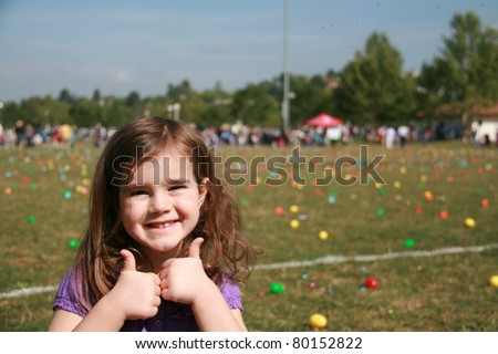 Thumbs-up Adorable girl in front of Easter egg covered field