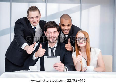 Thumbs up business. Four smiling successful businesspeople sitting at table in office while discussing their business doing. Young people show a thumbs up #227927446
