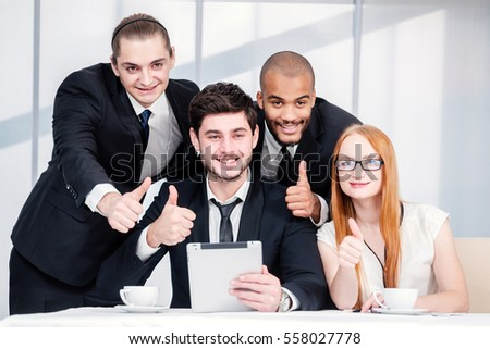 Thumbs up business. Four smiling successful businesspeople sitting at table in office while discussing their business doing. Young people show a thumbs up #558027778