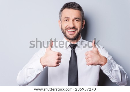Thumbs up for success! Happy mature man in shirt and tie showing his thumbs up and smiling while standing against grey background
