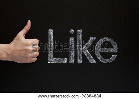 Thumbs up in front of a blackboard with the word Like written with white chalk on it.