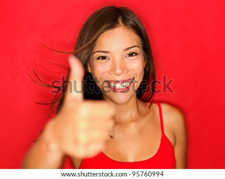 Thumbs up like woman smiling happy with natural beautiful smile on red background. Cheerful and joyful multiracial Asian / Caucasian girl looking energetic at camera showing positive hand sign.