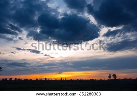 Thunder Sky. Dark, heavy clouds against the background of sunset. #652280383