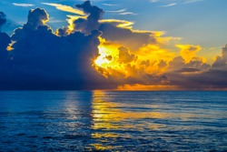 Thunder storms and clouds on the horizon as the sun bursts through reflecting on the calm Atlantic ocean off the coast of Florida