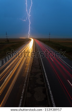 Thunderstorm and lightnings in night over highway with cars moving