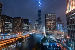 Thunderstorm in Chicago city by night, lighting on a rod of a skyscraper. Buildings by night during a stormy night. Impressive flash during a big thunderstorm in downtown. Tower and light