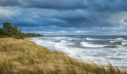 Thunderstorm over Baltic sea in a windy summer evening. Impressive waves hitting breakwater. Lighthouse covered in dark storm clouds above. Sandy seashore covered in tall grass.