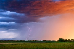 Thunderstorm with lightning bolt and dramatic storm clouds over a field at sunset