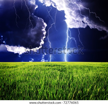 Thunderstorm with lightning in green meadow. Dramatic sky.