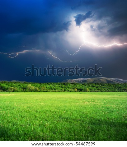 Thunderstorm with lightning  in green meadow. Nature composition.