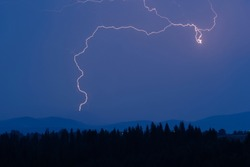 Thunderstorm with lightning on the mountain. Thunderstorms on a mountain plateau with thunderstorms after sunset. Thunderstorms and storm over pine forest in summer.
