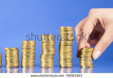 Thus based Capital. Steps up of golden coins and hand is building coins isolated on blue background
