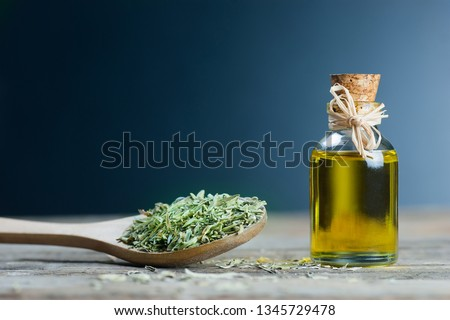 thyme essential oil and Heap of dry thyme in wooden spoon or shovel on wooden background. Dried spice zahter thyme and oil concept Stock photo ©