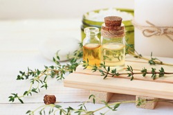 Thyme essential oil. Bottles with extract, fresh green plant leaves. Aromatherapy treatment.