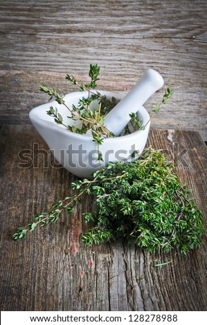 Thyme in a white mortar on a wooden background